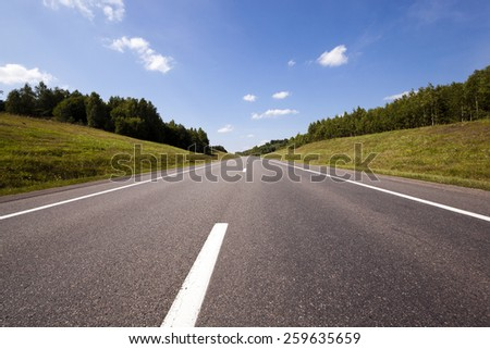 the small rural asphalted road photographed in summertime of year. Belarus - stock photo