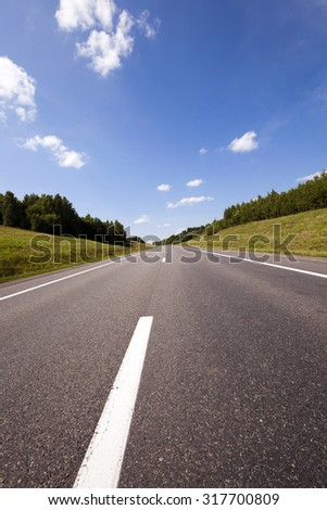 the small rural asphalted road photographed in summertime of year. Belarus