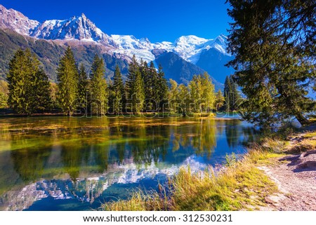 The snow-covered Alps and evergreen fir-trees  reflected in lake. Early fall in Chamonix, Haute-Savoie - stock photo