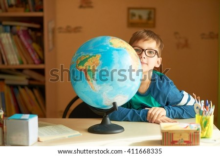 the student studies the globe. Schoolboy with globe. boy with globe