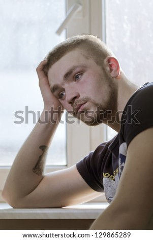 The thoughtful guy sits at a window - stock photo