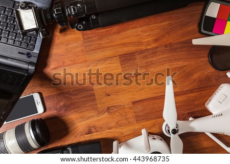 The tools of a professional photographer and video on wooden background  - stock photo