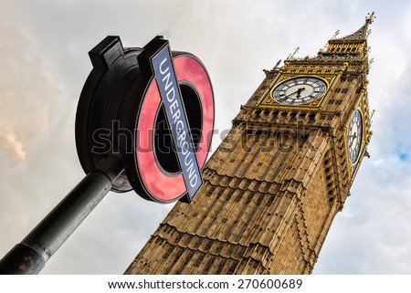 The 'Underground' sign and 'Big Ben' tower - stock photo