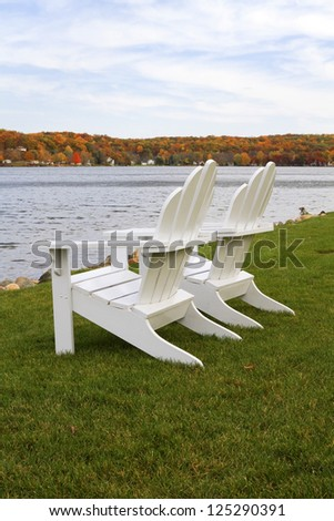 """The View"" -- Chairs sit along the edge of Gun Lake during the autumn season in Michigan. - stock photo"