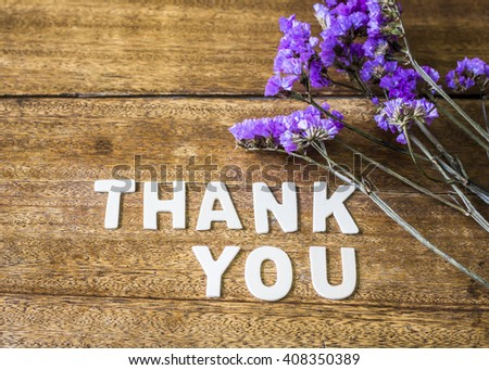 the word Thank You design by white letter press with dry flowers on wooden table - stock photo
