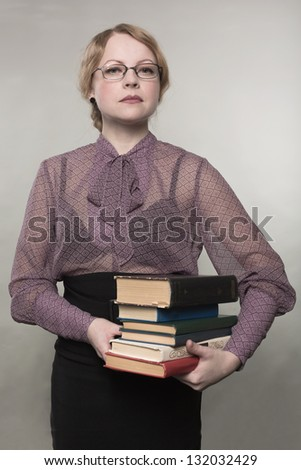 The young woman holds a pile of books - stock photo