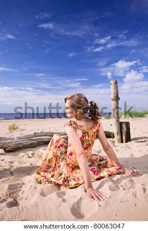 The young woman in orange dress on a beach. - stock photo