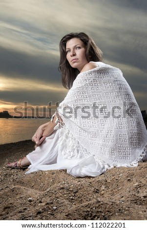 The young woman sits on a beach in a white dress - stock photo