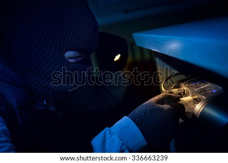 Thief inserting usb flash memory into computer and stealing data - stock photo