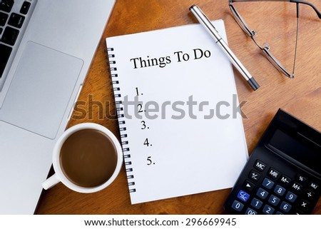 """""""Things To Do"""" text on notebook with a cup of coffee, calculator, spectacle and laptop on desk - stock photo"""