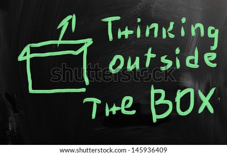 """Think outside the box"" handwritten with white chalk on a blackboard - stock photo"