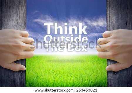 """Think outside the box"" Motivational quotes. Hands opening a wooden door then found a texts floating among new world as green grass field, Blue sky and the Sunrise. - stock photo"