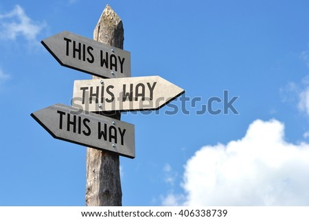 """""""This way, this way, this way"""" - wooden signpost, cloudy sky - stock photo"""