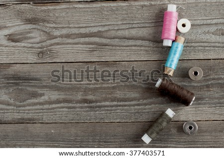 thread reels with spools on wooden background. - stock photo
