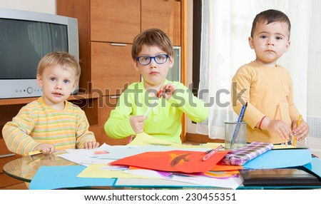 Three   children drawing with crayons at  table. - stock photo