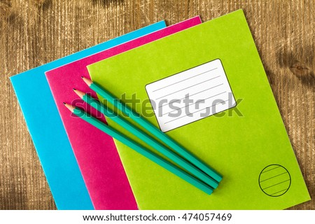 Three colored exercise books and three pencils on the wooden background