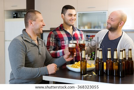 Three fun guys drinking beer,eating chips and laughing at house party - stock photo