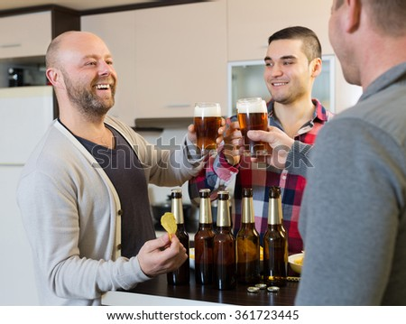 Three guys drinking beer,eating chips and laughing at house party - stock photo
