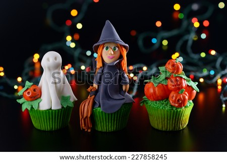 Three Halloween cupcakes decorated with sugar figures of witch ghost and pumpkins.  - stock photo