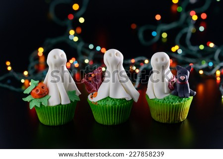 Three Halloween cupcakes decorated with sugar ghosts. - stock photo