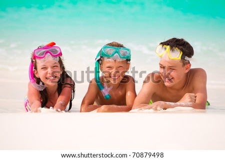 Three happy children on beach with colorful face masks and snorkels, sea in background. - stock photo
