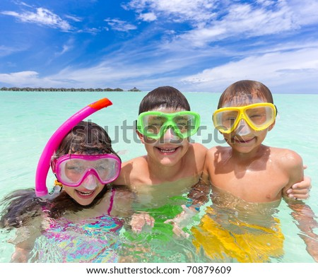 Three happy young children in tropical sea with snorkels and face masks, blue sky and cloudscape background. - stock photo