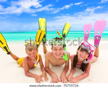 Three happy young children with colorful snorkels and flippers on sandy tropical beach, sea and cloudscape background. - stock photo