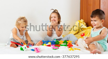 Three little children playing on  bed in  bedroom. - stock photo