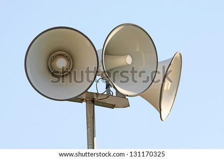 Three megaphones in blue sky background - stock photo