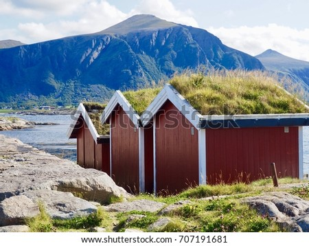 Three red wood huts with grass covered roofs on coast with view from the Atlantic ocean scenic road in Norway.