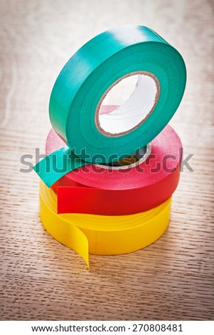 three rolls of insulating tape on wooden board close up  construction concept - stock photo
