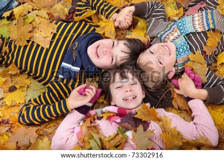 Three siblings laying in autumn leaves. - stock photo