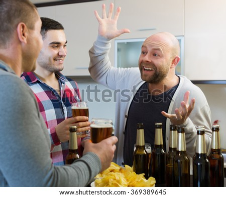 Three smiling european guys drinking beer and laughing at house party - stock photo