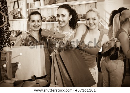 Three young cheerful girls shopping together and chatting in the fashion store - stock photo