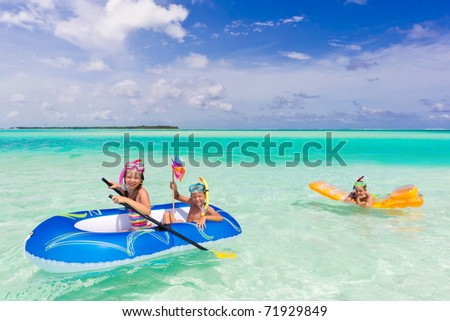 Three young children playing on lilo and dinghy in tropical sea with blue sky and cloudscape background. - stock photo