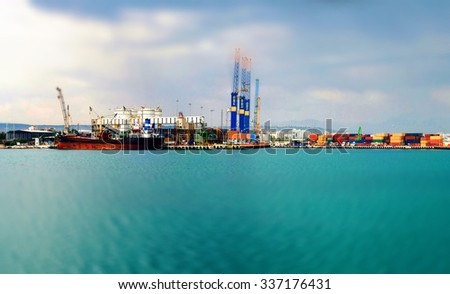 Tilt-shift panoramic view of sea port with ship, cargo, containers and lorry - stock photo