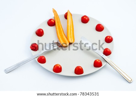 """""""Time for diet"""" funny theme - plate with cherry tomatoes and carrot set as the clock - stock photo"""