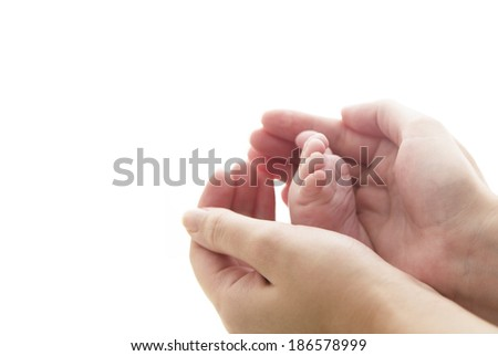 Tiny Newborn Baby's feet on mother's hands closeup. Mom and her Child. Beautiful  Conceptual image of Maternity  - stock photo