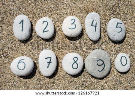0 to 9 digits on group of stones with sand background - stock photo