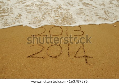 2013 to 2014 new year sign written in sand with waves lapping at the edge, symbolising change of year. - stock photo