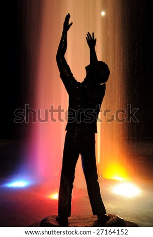 """To Worship God"" -- A silhouetted statue with a lighted water fountain in the background."