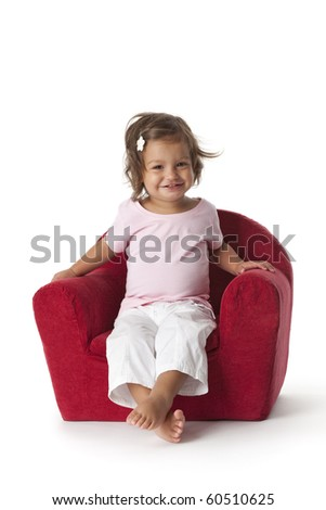 Toddler girl making fun in an armchair on white background