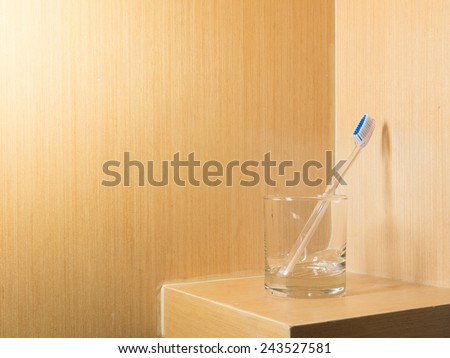 toothbrush in the glass with warm light bathroom - stock photo