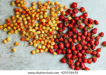 Top view.Fresh fruits. Ripe juicy delicious strawberries and yellow cherries on white background. - stock photo