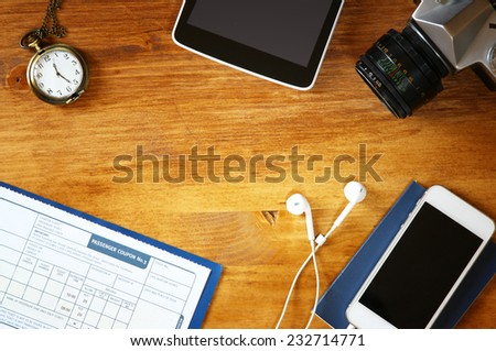 top view image of phone with empty screen, old camera passport and flight boarding pass. - stock photo