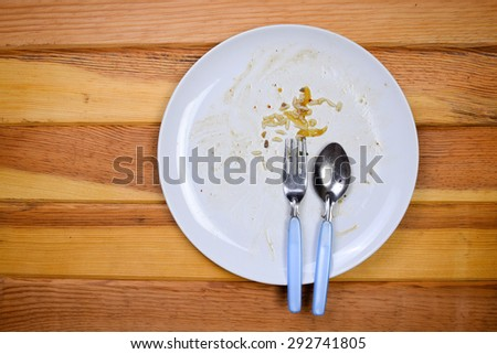 Top view of empty plate, dirty after the meal is finished. - stock photo