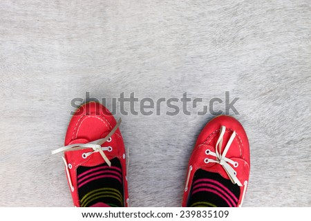 top view of red worn girl shoes over wooden textured background  - stock photo