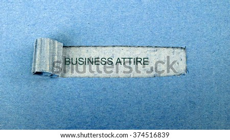 """Torn blue paper on dull blue surface with """"business attire""""                              - stock photo"""