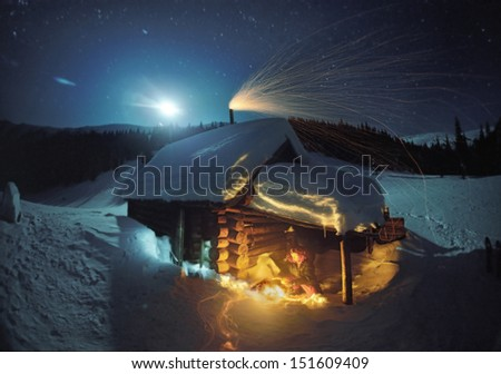 Tourist heated by the fire in a cold night, near-summer dwelling shepherds ..  Moon beckons in a mystical glow a lone traveler in the bitter cold has found shelter at an abandoned cabin in the forest - stock photo