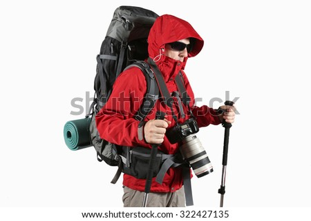 tourist photographer in a red jacket with a gray backpack and trekking sticks